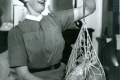 07_District nurse - midwife Catriona MacAskill weighing a baby in North Uist, Scotland, 'he's put on weight!' -c.1959