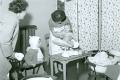 District nurse weighing child at health clinic - 1950s